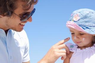 Pai apllicando protetor solar na filha