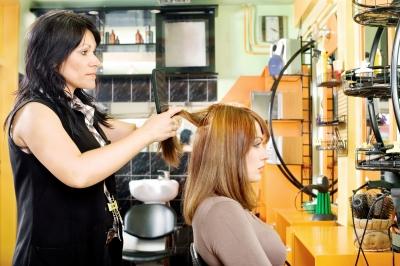 Cabeleireira alisando cabelo de cliente