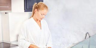 Mulher na cozinha cortando alimentos naturais