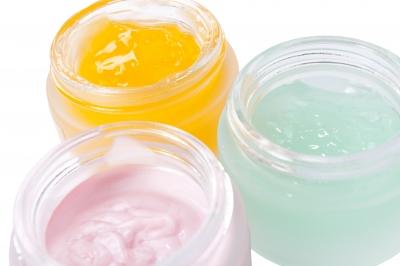 três potes com produtos cosméticos em apresentação de creme, gel e gel-creme.