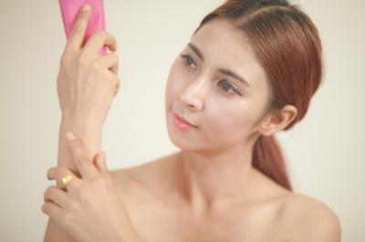 Mulher aplicando produto cosmético na pele.