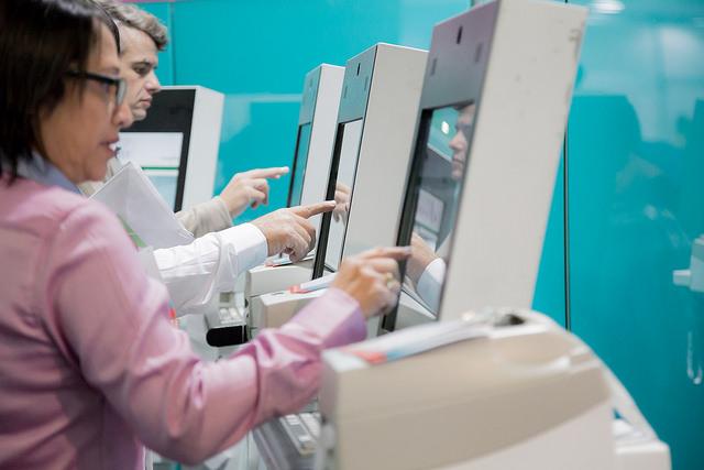 Visitantes da FCE Cosmetique realizando a impressão dos crachás após já terem feito credenciamento online.