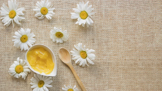 creme de manteiga de karité sobre mesa com flores de camomila