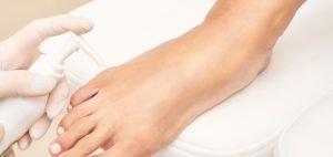 Massagem com creme de ureia nos pés para ação queratolítica.